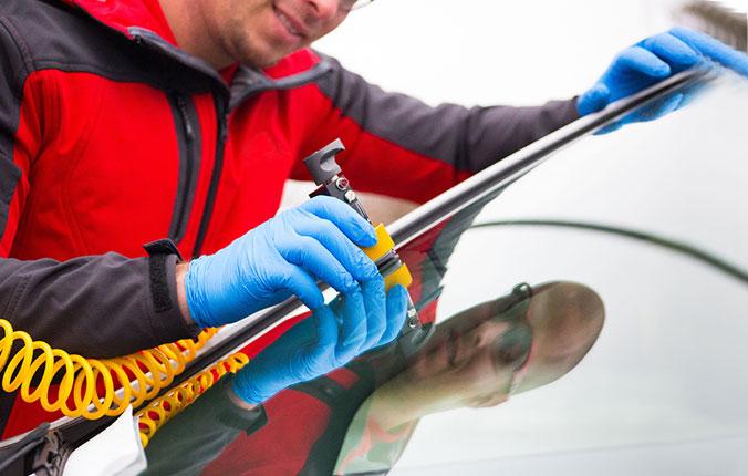 Safelite tech replacing windshield on car